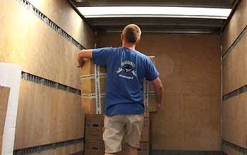 Umzugshelfer Umzusgengel trägt Karton in Umzugswagen