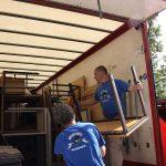 Zwei Umzugshelfer laden Möbel in Umzugswagen bei Büroumzug