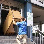 Mitarbeiter von Umzugsengel trägt Holzschrank bei Firmenumzug ins Gebäude