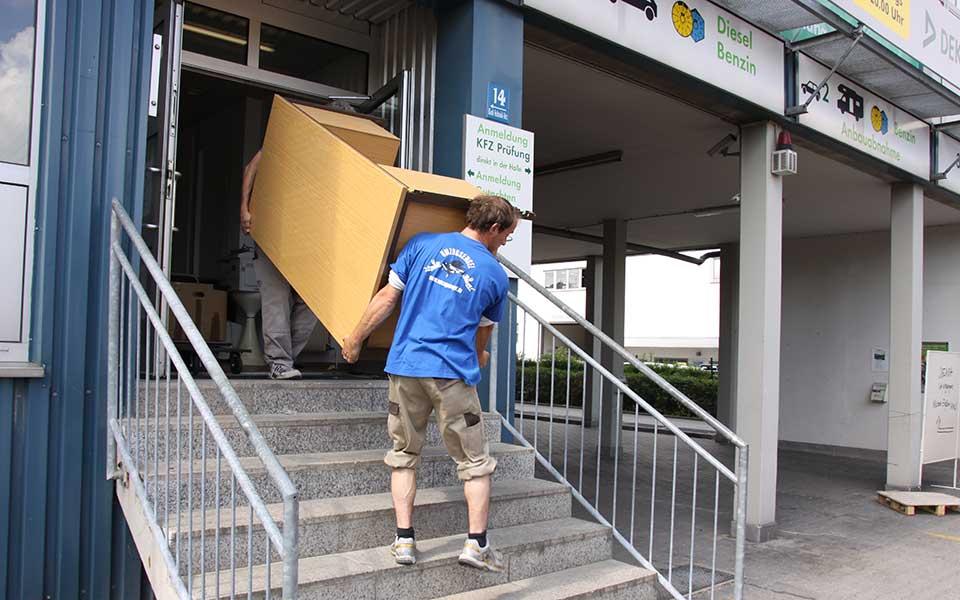 Umzugshelfer tragen Holzschrank aus Firma bei Firmenumzug München