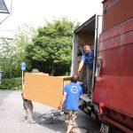 Umzugshelfer laden Möbel bei Büroumzug in Umzugswagen