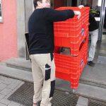 Umzugshelfer tragen PC-Rollwannen bei Büroumzug