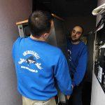 Zwei Umzugsengel Mitarbeiter tragen Schränkchen bei Firmenumzug München