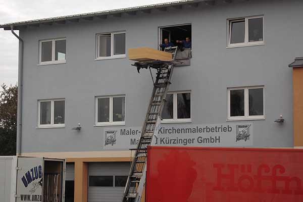 Fernaufnahme Umzugshelfer transportieren Holzschrank mit Möbellift aus Fenster