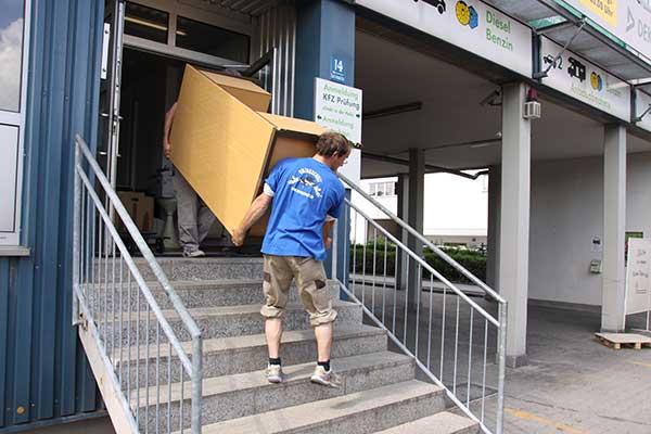 Zwei Helfer tragen Holzschrank bei Firmenumzug aus Gebäude