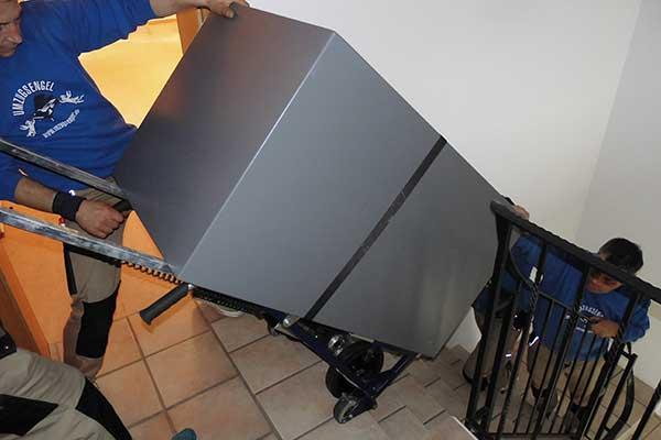 Zwei Umzugshelfer transportieren schweres Möbelstück treppauf