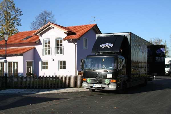 Privatumzug schwarzer Möbelwagen Umzugsengel auf Straße